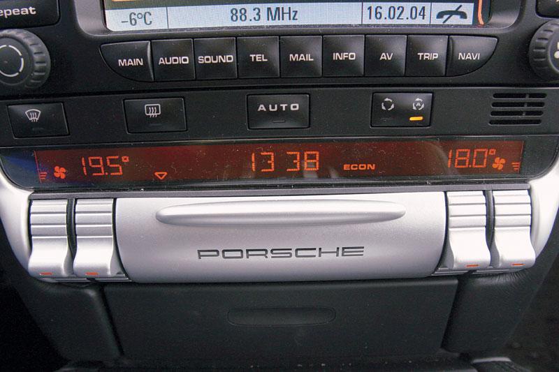 Под огромным информационным экраном приютился скромный блок управления климат-контролем: ручки-джойстики удобны, а вот световая индикация мелкая и тусклая. Под опускаемой крышечкой с надписью Porsche скрыты дополнительные клавиши